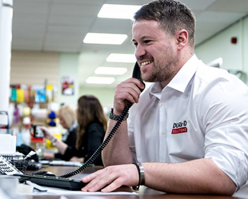 Member of Dura on the phone to a customer